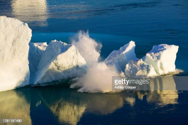an arched iceberg collapsing into the sea from the jacobshavn glacier or sermeq kujalleq which drains 7% of the greenland ice sheet and is the largest glacier outside of antarctica. - glacier collapsing stock pictures, royalty-free photos & images