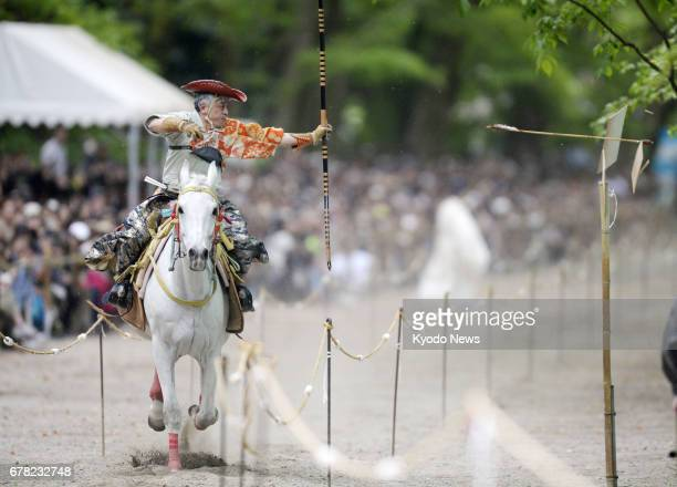 An archer dressed in traditional attire shoots an arrow while riding a horse at full speed during the annual Yabusame Shinji event at Shimogamo...