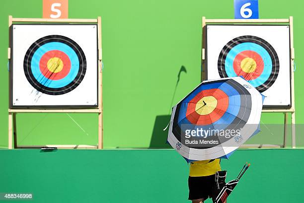 An archer holding an umbrella with a target design checks the target during the first day of the Archery test event for the Rio 2016 Olympic Games at...