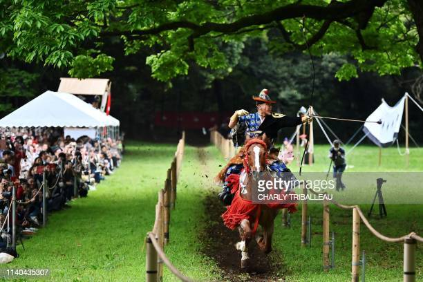 TOPSHOT An archer on horseback dressed as an ancient samurai warrior shoots an arrow at a target during an event to celebrate Japan's new imperial...