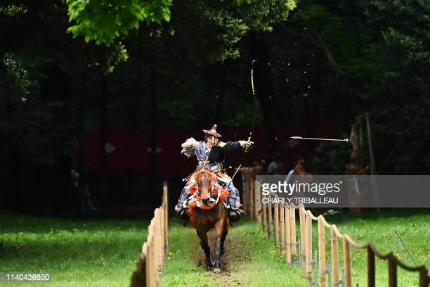 An archer on horseback dressed as an ancient samurai warrior shoots an arrow at a target during an event to celebrate Japan's new imperial Reiwa era...
