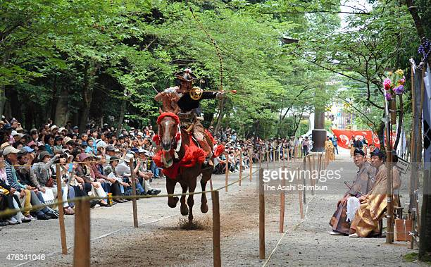 An archer on the horse back takes aim during the 'Yabusame' ritual at Omi Jingu Shrine on June 7 2015 in Otsu Shiga Japan The ritual takes place in...