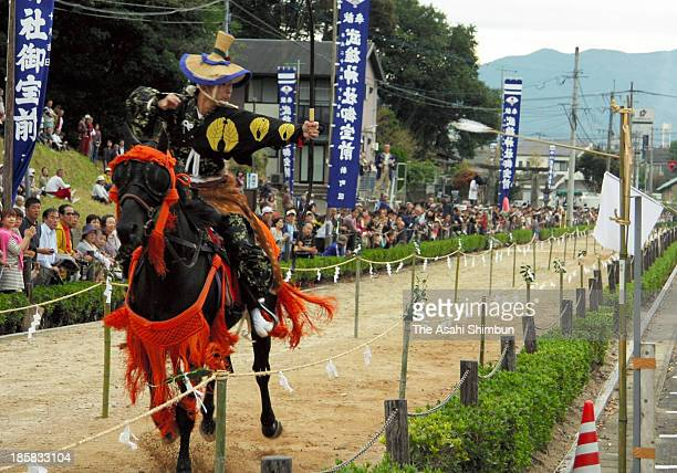 An archer on the running horseback aims at a target at Takeo Shrine on October 23 2013 in Takeo Saga Japan