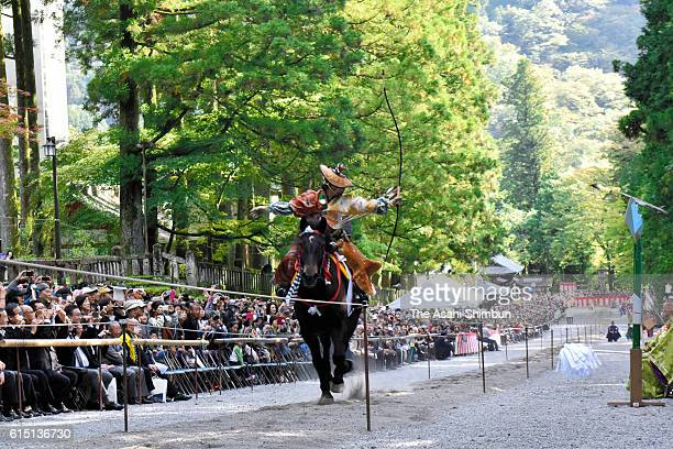 An archer takes aim during the 'Yabusame' horseback archery at the main approach of the Nikko Toshogu Shrine on October 16 2016 in Nikko Tochigi Japan
