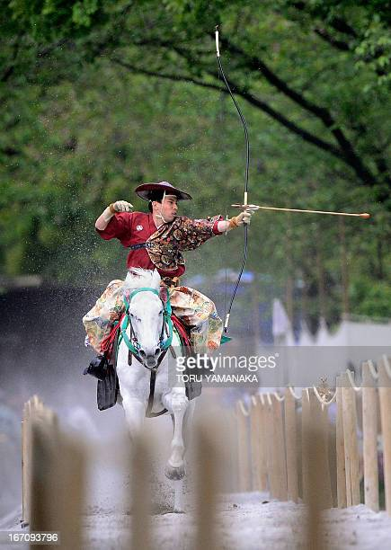 An archer wearing a samurai costume riding on horseback shoots an arrow to a target at Sumida Park in Tokyo on April 20 2013 The archer was taking...
