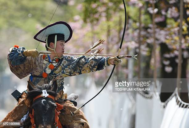 An archer wearing ancient samurai warrior dress shoots an arrow towards the target while riding on horseback during a Yabusame demonstration of the...