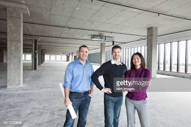 An architect and two owners of a new raw business space standing in a line.