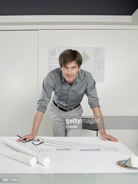 An architect leaning over blueprints on a desk