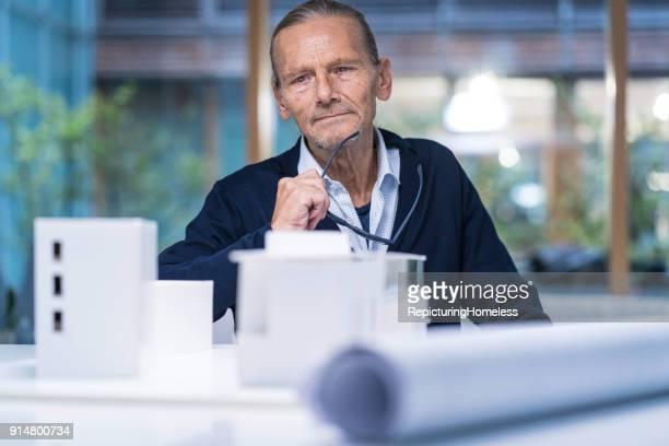 Architekt sitzt hinter seinen Modellen und schaut in die Kamera