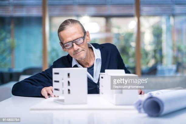 architekt schaut sich sein modell - repicturing homeless stock-fotos und bilder
