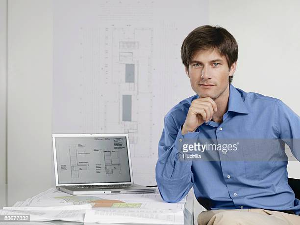 an architect sitting at his desk with a laptop and architectural drawings - あご ストックフォトと画像