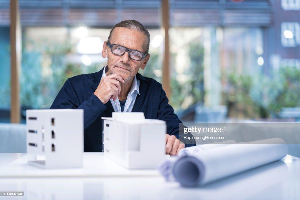 Architekt schaut sich nachdenklich sein Modell an : Stock-Foto
