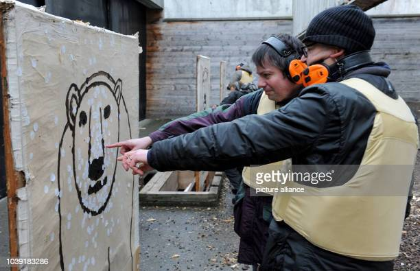 An Arctic reasearcher along with shooting instructor Dirk Mengedoht analyses his hit rate on a polar bear shaped target at a shooting range in...