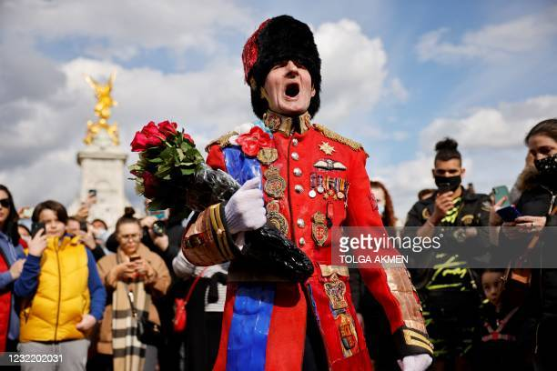 An ardent Royals fan carries a floral tribute to lay at the front of Buckingham Palace in central London on April 9, 2021 after the announcement of...