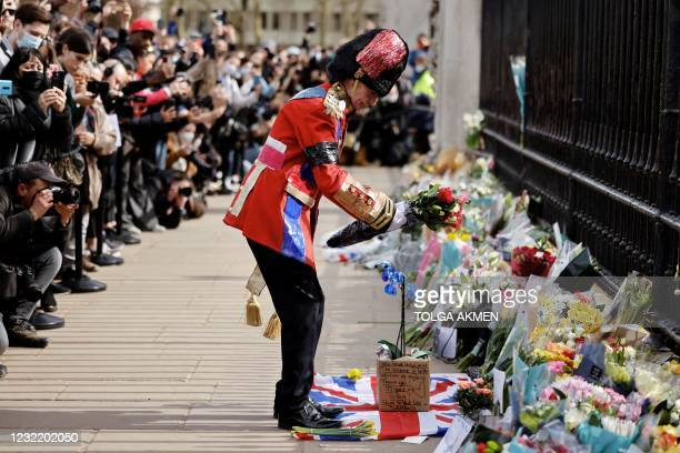 An ardent Royals fan lays a floral tribute at the front of Buckingham Palace in central London on April 9, 2021 after the announcement of the death...