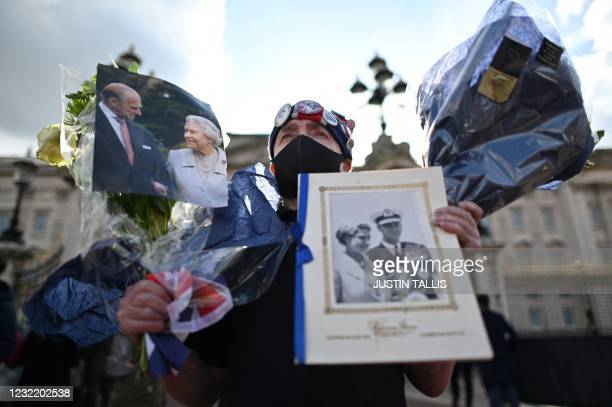 An ardent Royals supporter holds tributes at the gates of Buckingham Palace in central London on April 9, 2021 after the announcement of the death of...