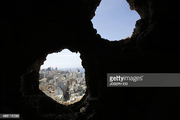 An area of West Beirut is seen through a hole from the abandoned building of the Holiday Inn hotel in Beirut on April 11 2014 A symbol of Lebanon's...