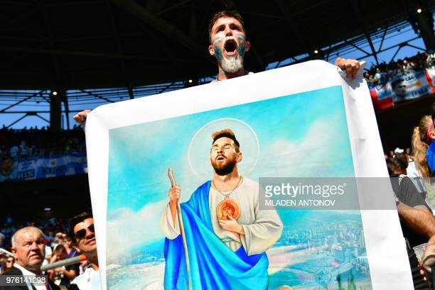 TOPSHOT An Argentina fan holds a drawing of Argentina's forward Lionel Messi depicting him as Jesus before the Russia 2018 World Cup Group D football...