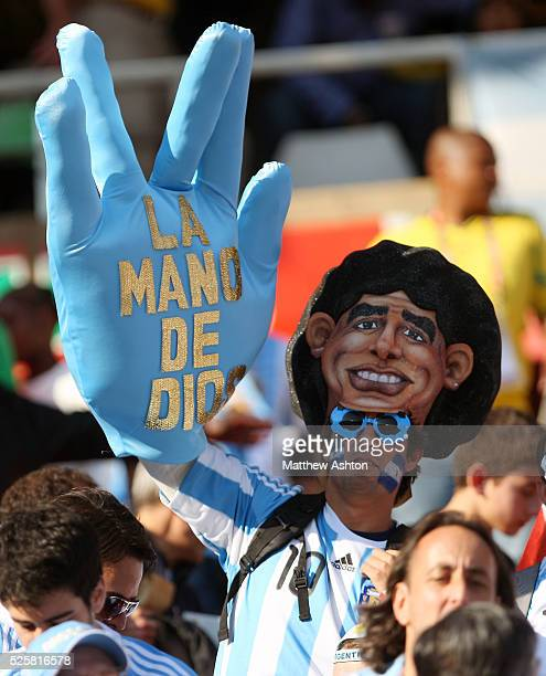 An Argentina fan wearing a mask of Diego Maradona holda up a giant hand with the words the hand of god in Spanish