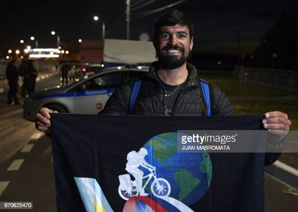 An Argentina supporter who biked from Cordoba Argentina to Bronnitsy Russia poses with a banner after the squad arrives at their base camp in...