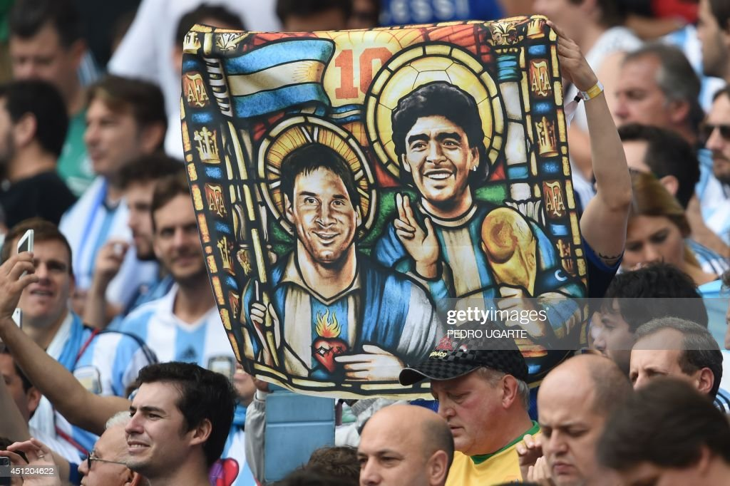 An Argentina's fan holds an image of Argentina's forward Lionel Messi and former footballer Diego Maradona as Saints, before for the Group F football match between Nigeria and Argentina at the Beira-Rio Stadium in Porto Alegre during the 2014 FIFA World Cup on June 25, 2014. AFP PHOTO / PEDRO UGARTE