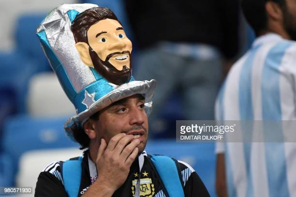 An Argentina's fan wearing a fancy hat depicting Argentina's forward Lionel Messi reacts after being defeated by Croatia at the end of the Russia...