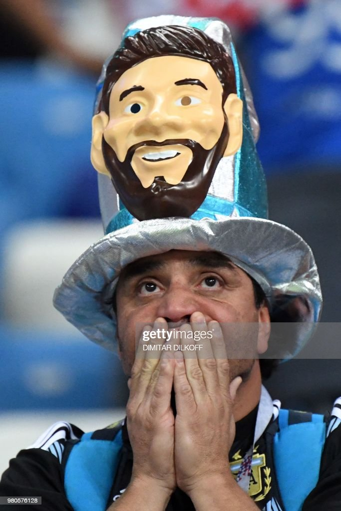 TOPSHOT - An Argentina's fan wearing a fancy hat depicting Argentina's forward Lionel Messi reacts after being defeated by Croatia at the end of the Russia 2018 World Cup Group D football match between Argentina and Croatia at the Nizhny Novgorod Stadium in Nizhny Novgorod on June 21, 2018. (Photo by Dimitar DILKOFF / AFP) / RESTRICTED