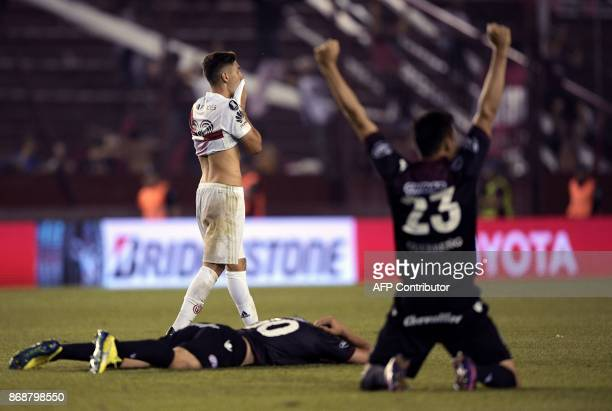 An Argentina's River Plate player reacts as Argentina's Lanus footballers celebrate after defeating River Plate by 42 and qualifying for the Copa...