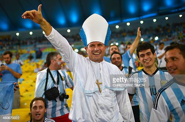 An Argentina's soccer fan dressed like pope Francis cheers at the Maracana Stadium in Rio de Janeiro on June 15 2014 before the start of the 2014...