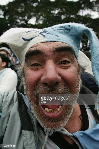 An Argentine fan celebrates a goal as they watch the FIFA World Cup South Africa 2010 football match against Mexico on an outdoor screen in Buenos...