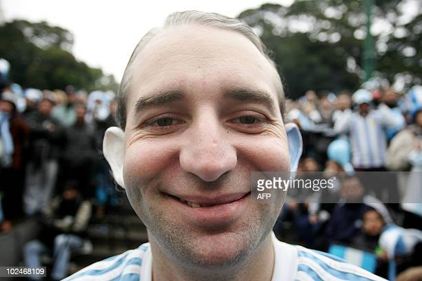 An Argentine fan is seen with his ears painted with the Argentine colours as he watches the FIFA World Cup South Africa 2010 football match against...
