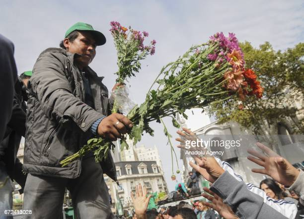 An Argentine farmer delivers free flowers during a peasant protest against the high cost of living of small farmers and the demand for credit to buy...