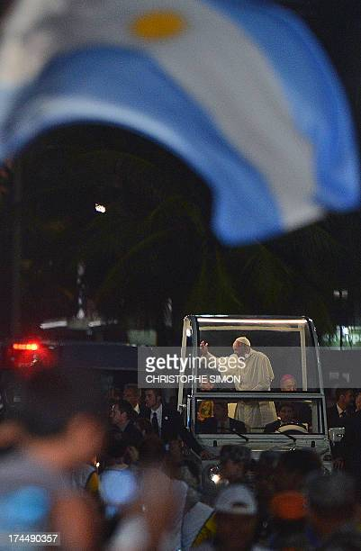 An Argentine flags flutters as Pope Francis waves at faithfuls standing on the beachfront while he arrives on the popemobile at Copacabana beach to...
