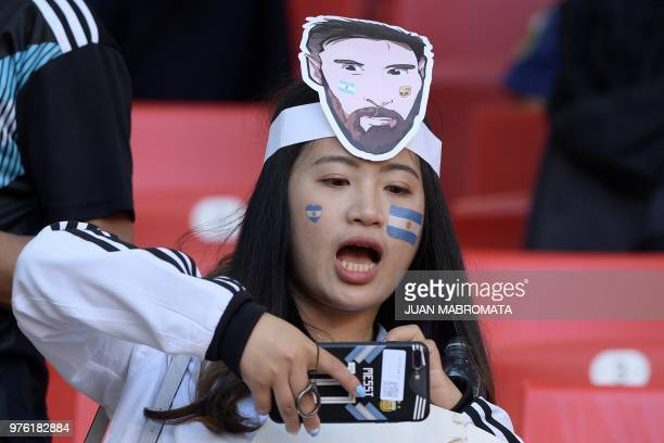 An Argentine's supporter wears a mask depicting Argentina's forward Lionel Messi during the Russia 2018 World Cup Group D football match between...