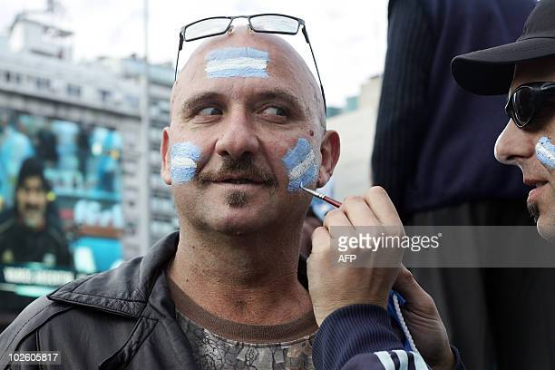 An Argentinian fan has his face painted with the national colours as he watches the South Africa 2010 World Cup match against Germany on an outdoor...