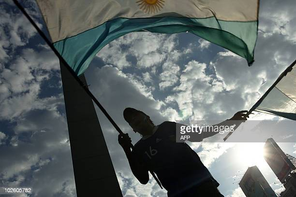 An Argentinian fan waves a flag as he watches the South Africa 2010 World Cup match against Germany on an outdoor screen in Buenos Aires Argentina on...