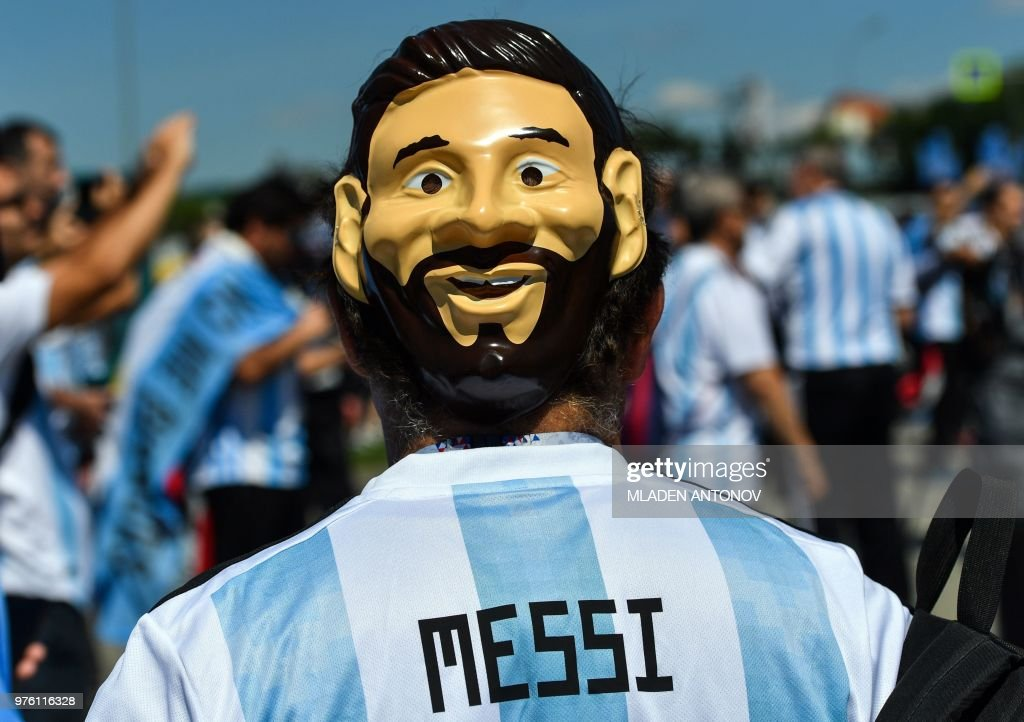 TOPSHOT - An Argentinian fan with a mask depicting Lionel Messi walks outside the Spartak Stadium ahead of the Russia 2018 World Cup Group D football match between Argentina and Iceland in Moscow on June 16, 2018. (Photo by Mladen ANTONOV / AFP) / RESTRICTED