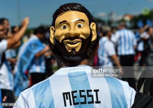 TOPSHOT An Argentinian fan with a mask depicting Lionel Messi walks outside the Spartak Stadium ahead of the Russia 2018 World Cup Group D football...