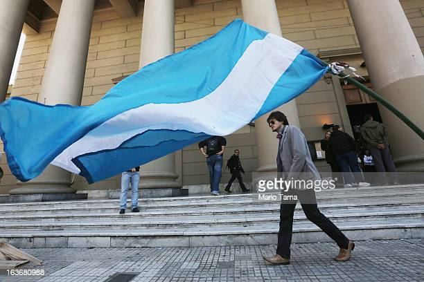 An Argentinian flag flies as people walk past the Metropolitan Cathedral on the day after Pope Francis was elected at the conclave on March 14 2013...