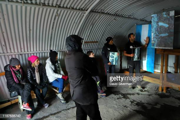 An Argentinian guide describes to tourists in a glacial research station quonset hut how the Upsala glacier has receded in the past 90 years during...