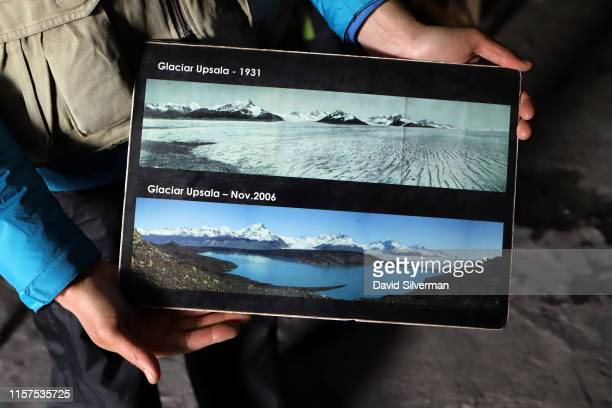 An Argentinian guide holds photographs showing how the Upsala glacier has receded in the past 90 years during a tourist discovery tour of the...