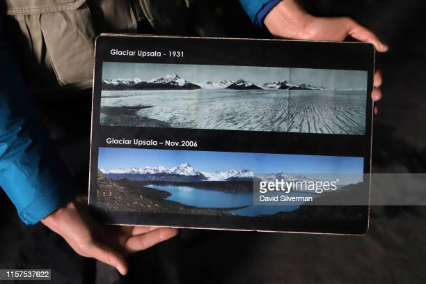 An Argentinian guide holds photographs showing how the Upsala glacier part of the Southern Patagonian Ice Field has receded in the past 90 years...