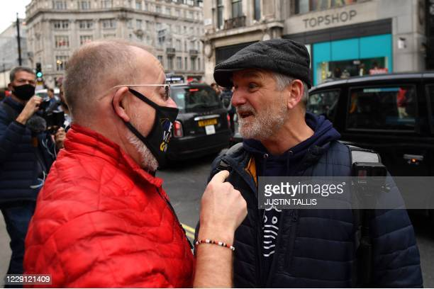 An argument takes place between a passer-by and a protester on Oxford Street at a demonstration against vaccinations and government restrictions...