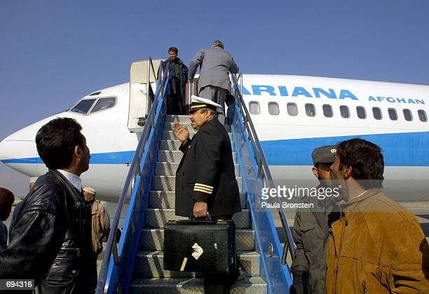 An Ariana Afghan Airlines pilot boards a 727 before the airlines'' first international flight in five years January 24 2002 at Kabul Airport in Kabul...