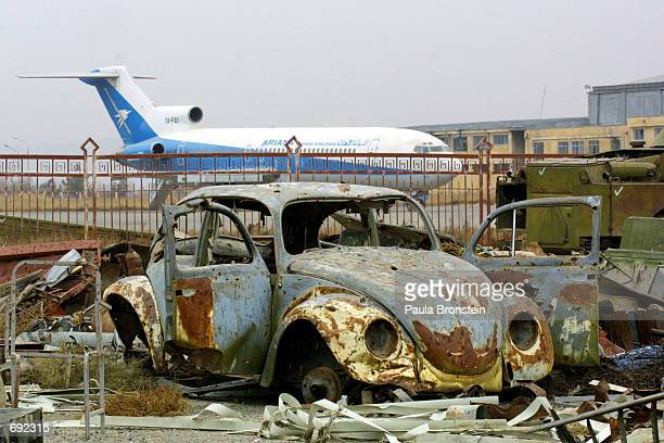 An Ariana Afghan Airlines plane sits on the tarmac at the Kabul airport near a destroyed car and other debris January 10 2002 in Kabul Afghanistan...