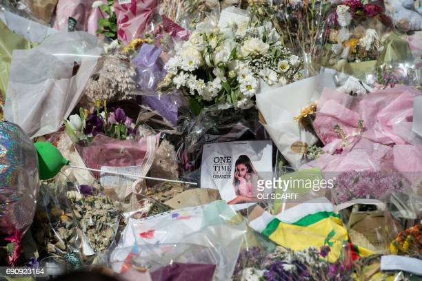 An Ariana Grande poster is placed amongst flowers and messages of support in St Ann's Square in Manchester northwest England on May 31 placed in...