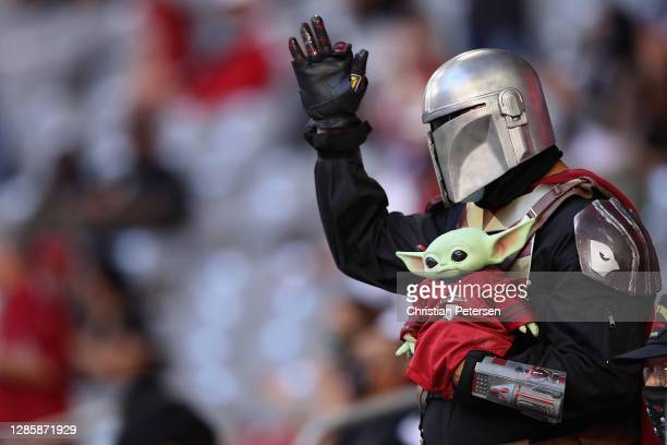An Arizona Cardinals' fan dressed as 'The Mandalorian' cheers during the NFL game against the Buffalo Bills at State Farm Stadium on November 15,...