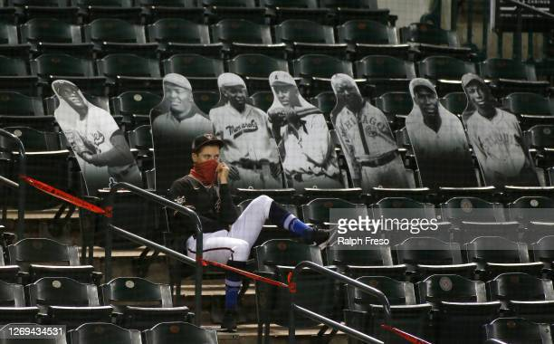An Arizona Diamondbacks player watches from the stands in front of cardboard cutouts of Jackie Robinson and members of the Negro National League...