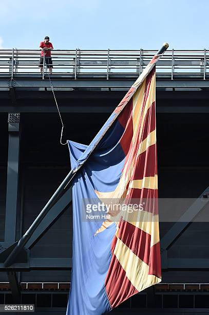 An Arizona Diamondbacks stadium worker on the catwalk attempts to untangle the Arizona State Flag with rope and a large hook prior to a game against...