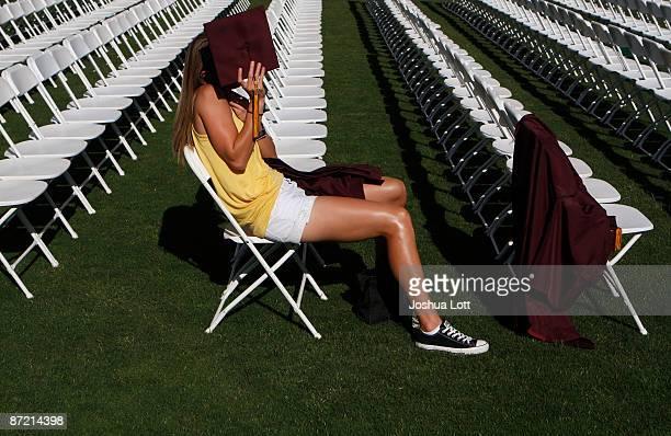 PHOENIX AZ MAY 13 An Arizona State University graduate student uses her cap to block the sun during her graduation at Sun Devil Stadium May 13 in...